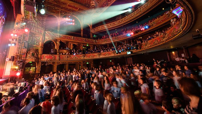 "HACKNEY, ENGLAND - DECEMBER 13: School children get out of their seats to dance during the finale of a performance of the traditional pantomime ""Sleeping Beauty"" at the Hackney Empire on December 13, 2016 in Hackney, England."