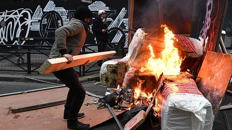 A protester throws wood on a barricade during demonstrations in Paris