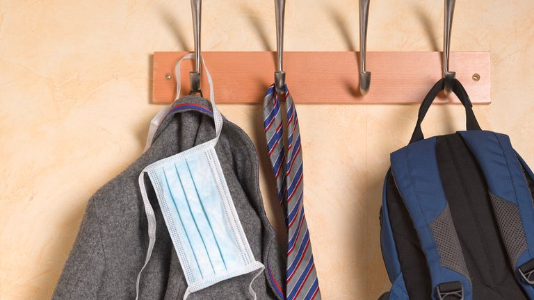 A school uniform hangs up with a face mask
