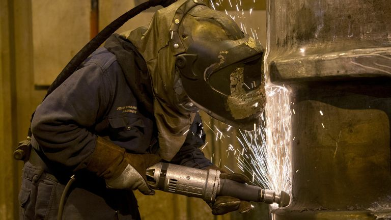 A grinder works on a freshly cast piece of steel in the foundry at Sheffield Forgemasters International Ltd