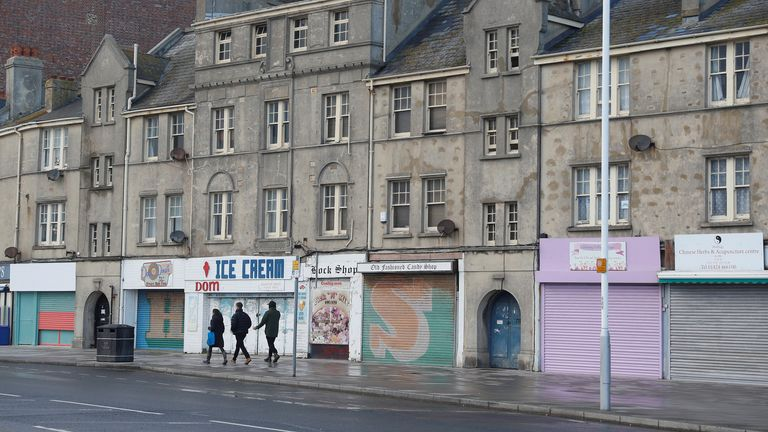 People walk past shuttered shops