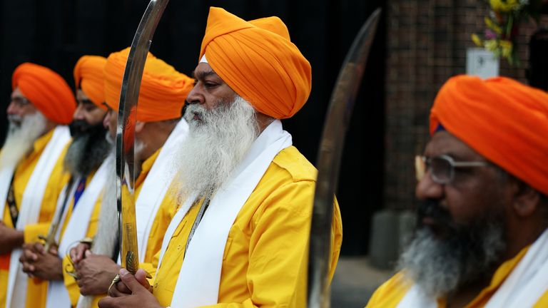 Five men representing the Panj Pyare - the five beloved - walk barefoot and carry swords in front of the procession as members of the Sikh community in Middlesbrough hold the Nagar Kirtan Sikh parade on July 21, 2019 in Middlesbrough, England.