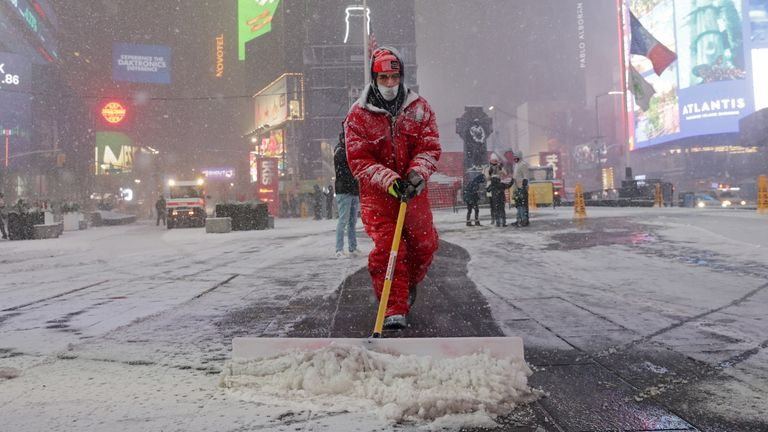 A worker clears snow as snow begins to fall in Times Square in New York City, New York