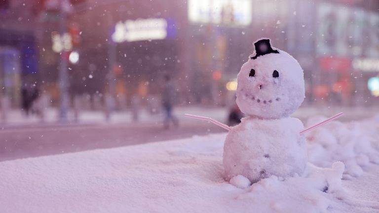 A snowman is seen as snow begins to fall in Times Square in New York City, New York