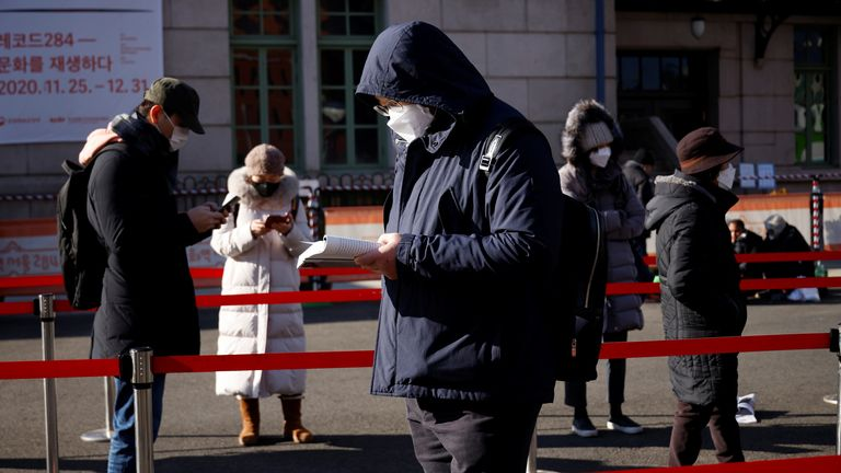 A man reads a book while waiting in a line to undergo coronavirus disease (COVID-19) test at a coronavirus testing site which is temporarily set up in front of a railway station on Christmas day in Seoul, South Korea, December 25, 2020. REUTERS/Kim Hong-Ji