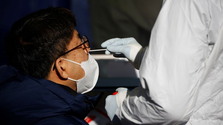 A man undergoes coronavirus disease (COVID-19) test at a coronavirus testing site which is temporarily set up in front of a railway station on Christmas day in Seoul, South Korea, December 25, 2020. REUTERS/Kim Hong-Ji