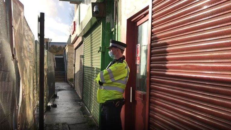 Screen grab of a Police officer outside the Pay and Sleep hostel in The Crescent, Southall, London, where shortly before 3pm on Friday, the body of a woman was found in a suitcase according to residents. The Metropolitan Police said the death is being treated as unexplained and inquiries to identify the woman are ongoing.