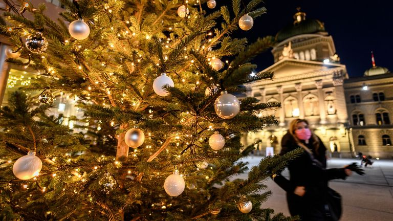 A woman wearing a protective face mask walks past a Christmas tree in front of the Swiss House of Parliament in Bern, Switzerland
