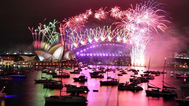 Fireworks explode on the Sydney Opera House and Sydney Harbor Bridge