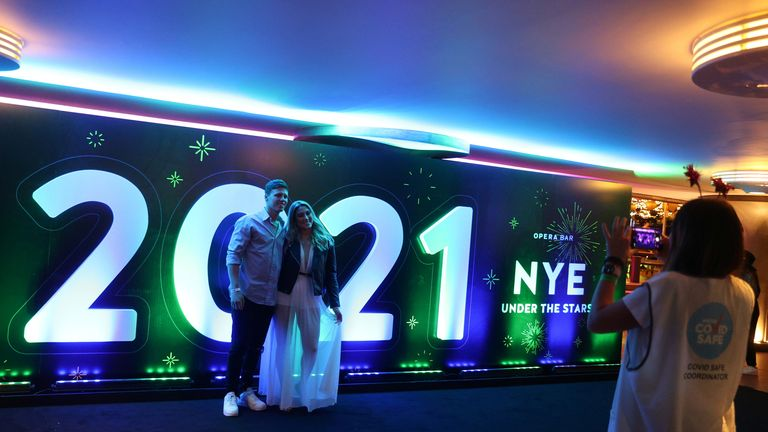 People begin celebrating New Year's Eve at the Sydney Harbour waterfront in Sydney