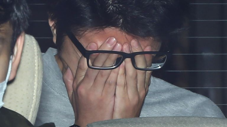 Suspect Takahiro Shiraishi covers his face with his hands as he is transported to the prosecutor's office from a police station in Tokyo on November 1, 2017. The 27-year-old Japanese man, who was arrested after police found nine dismembered corpses rotting in his house, has confessed to killing all his victims over a two-month spree after contacting them via Twitter, media reports. / AFP PHOTO / JIJI PRESS / STR / Japan OUT (Photo credit should read STR/AFP via Getty Images)