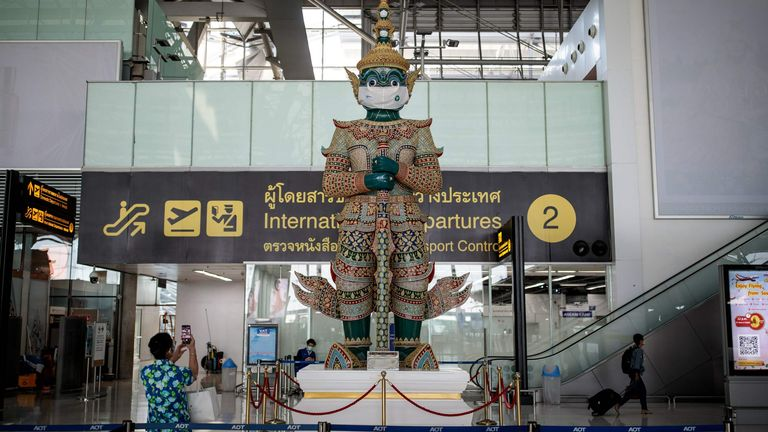 A traditional Thai statue wears a face mask as a campaign for travellers to prevent the spread of Covid-19 coronavirus at the departure terminal of Suvarnabhumi International Airport in Bangkok on December 18, 2020