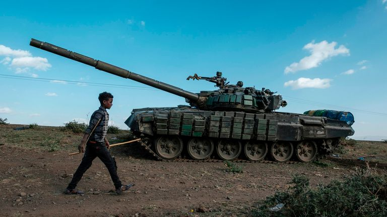 A shepherd walks in front of an abandoned tank belonging to Tigrayan forces in Ethiopia