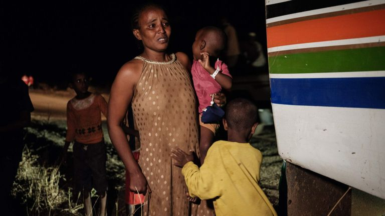 An Ethiopian refugee who fled Ethiopia's Tigray conflict, weeps next to her two children as she arrives in Sudan