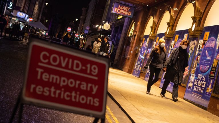 People wearing facemasks pass covid signage in Soho, London, after the second national lockdown ends and England has a strengthened tiered system of coronavirus restrictions.