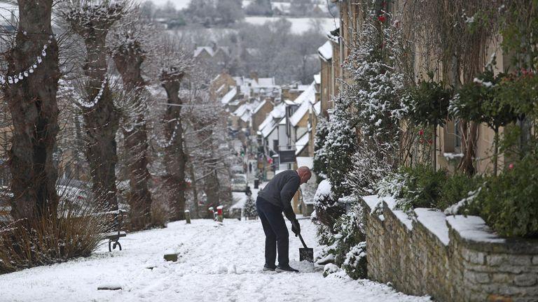 Seorang pria membersihkan salju dari jalur setapak di Burford, West Oxfordshire.