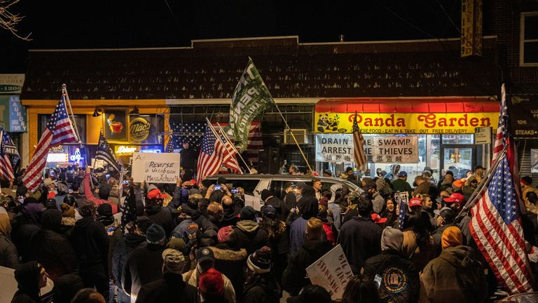 People demonstrate outside a now-shut restaurant against coronavirus restrictions