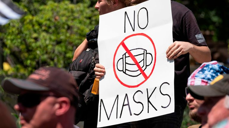 "An anti-mask protestor holds up a sign in front of the Ohio Statehouse during a right-wing protest ""Stand For America Against Terrorists and Tyrants"" at State Capitol on July 18, 2020 in Columbus, Ohio"