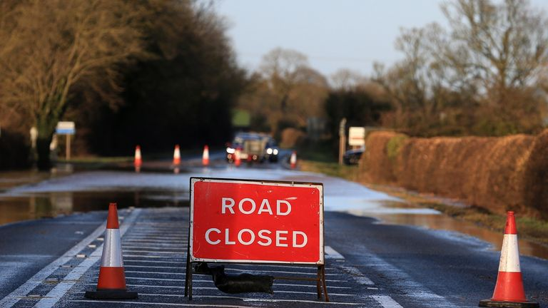 """A """"Road Closed"""" sign stands in front of floodwater after the River Trent burst its banks, near Lowdham, Nottinghamshire, in central England on February 16, 2020, after Storm Dennis caused flooding across large swathes of Britain. - A man died after falling into a river on Sunday as Storm Dennis swept across Britain with the army drafted in to help deal with heavy flooding and high winds. (Photo by Lindsey Parnaby / AFP) (Photo by LINDSEY PARNABY/AFP via Getty Images)"""