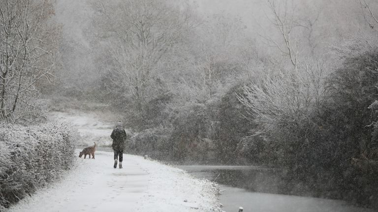 A dog walker braves the snow at Woolsthorpe Locke in Leicestershire.