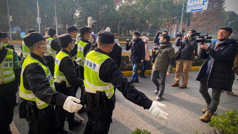 Police attempt to stop journalists from recording footage outside the Shanghai Pudong New District People's Court, where Chinese citizen journalist Zhang Zhan - who reported on Wuhan's Covid-19 outbreak and placed under detention since May - is set for trial in Shanghai on December 28, 2020. (Photo by Leo RAMIREZ / AFP) (Photo by LEO RAMIREZ/AFP via Getty Images)