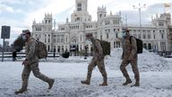 Members of the military walk past the Cibeles fountain and the City Hall building after a heavy snowfall in Madrid, Spain January 10, 2021. REUTERS/Susana Vera