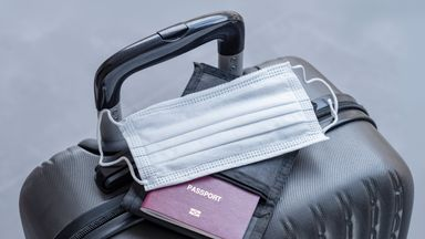 Passport and medical mask on travel suitcase. Concept the ban on travel during of the epidemic.