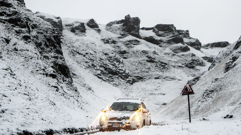A car navigates snowy conditions near Mam Tor in Derbyshire.