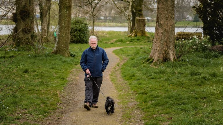 A man taking his daily exercise while walking his dog alone in an empty Scottish park. The public park is in Dumfries and Galloway, south west Scotland. Since the outbreak of Coronavirus members of the public must social distance and only go out to exercise once a day.