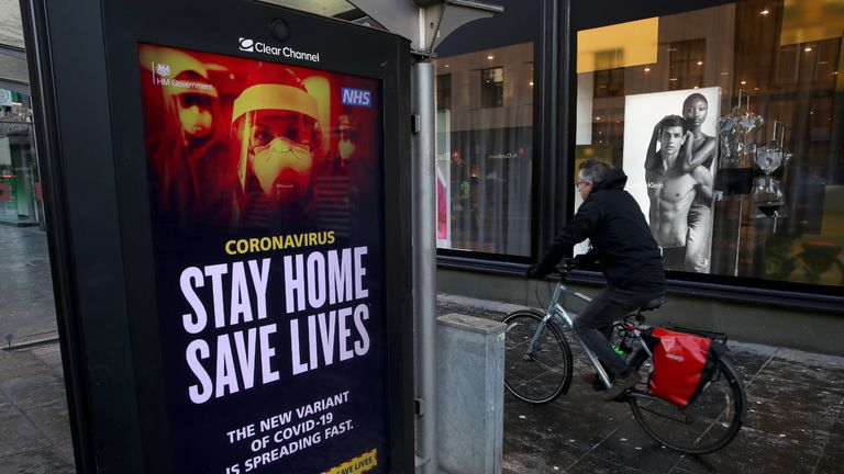 Members of the public cycles passed a coronavirus related advert on a bus stop in Glasgow , where strict lockdown measures for mainland Scotland are in force.