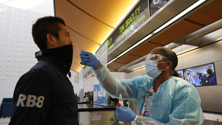 Scott Fujii, 34, is given a 24-hour rapid coronavirus test by nurse Caren Williams at Tom Bradley international terminal at LAX airport so he can travel to Hawaii to see family, as the global outbreak of the coronavirus disease (COVID-19) continues, in Los Angeles, California, U.S., November 23, 2020. REUTERS/Lucy Nicholson
