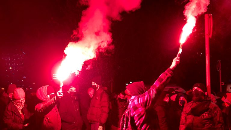 People light flares as they march near the ruling Law and Justice party headquarters in Warsaw, Poland. Pic: AP