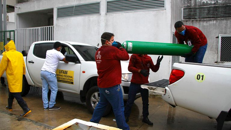 Amazonas Federal University's workers carry empty oxygen tanks at the Getulio Vargas Hospital amid shortages