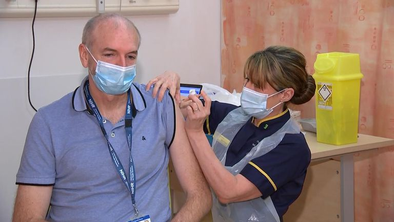 Andrew Pollard being vaccinated.