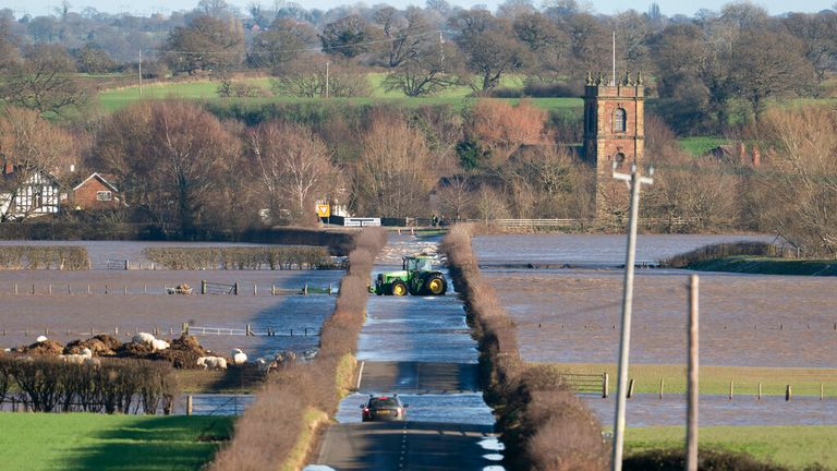 A tractor attempts to negotiate flood waters at Bangor-on-Dee, Wales. Pic: Associated Press