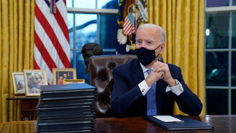 President Joe Biden waits to sign his first executive order in the Oval Office of the White House in Washington. As one of his first acts, Biden offered a sweeping immigration overhaul that would provide a path to U.S. citizenship for the estimated 11 million people who are in the United States illegally. It would also codify provisions wiping out some of President Donald Trump's signature hard-line policies, including trying to end existing, protected legal status for many immigrants brought
