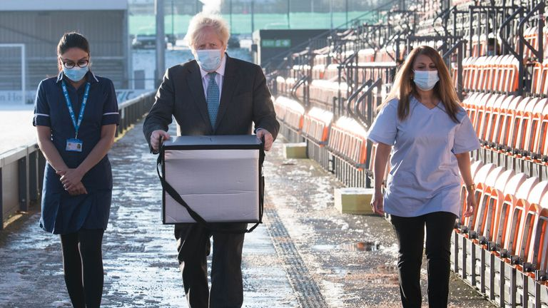 Prime Minister Boris Johnson loads doses of the Oxford/Astrazeneca coronavirus vaccine for mobile distribution at Barnet FC's ground, The Hive, north London