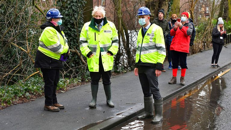 Boris Johnson talks with Environment Agency workers during his visit to Withington, Manchester. Pic: Associated Press