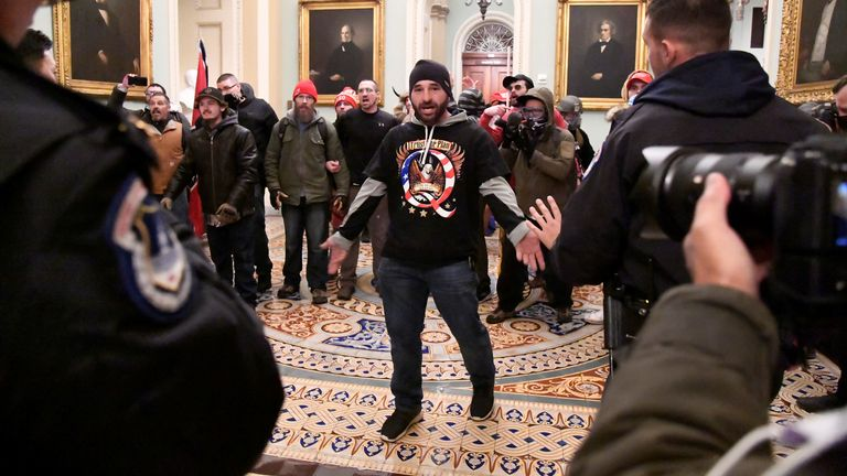 A supporter of President Donald Trump confronts police as Trump supporters demonstrate on the second floor of the U.S. Capitol near the entrance to the Senate after breaching security defenses, in Washington, U.S., January 6, 2021. REUTERS/Mike Theiler