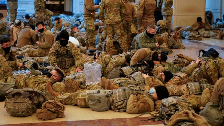 Several National Guard members are pictured lying on the floor of the U.S. Capitol