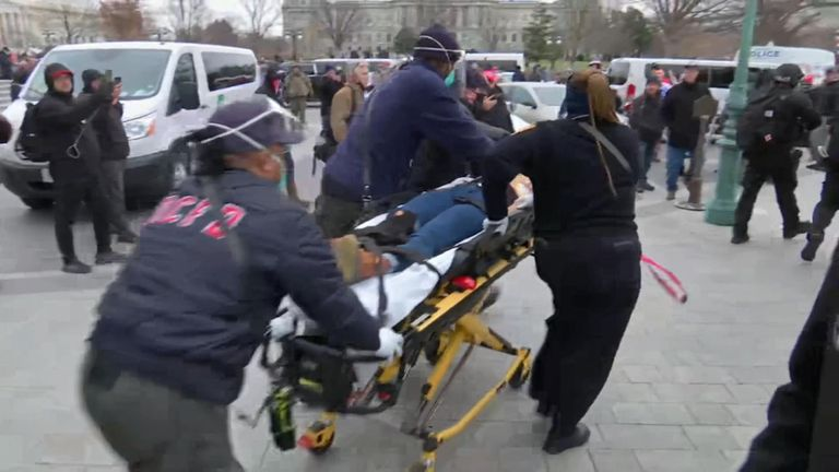 The shot woman is taken away by paramedics