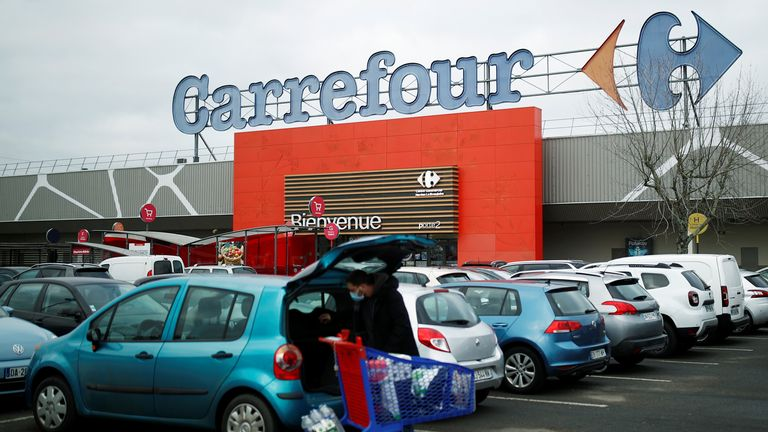 A customer empties his trolley in front of a Carrefour hypermarket store in Carquefou near Nantes, France January 13, 2021