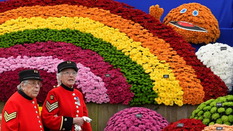 Two Chelsea Pensioners walk past a floral display based on children's television programs at the RHS Chelsea Flower Show at the Royal Hospital Chelsea, London, Britain, May 20, 2019. REUTERS/Toby Melville