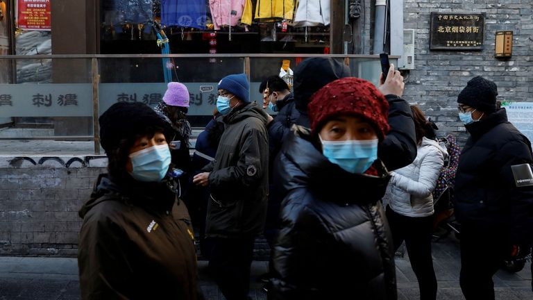People wearing face masks following the coronavirus disease (COVID-19) outbreak walk past shops along Yandaixiejie alley, in Beijing, China January 16, 2021.
