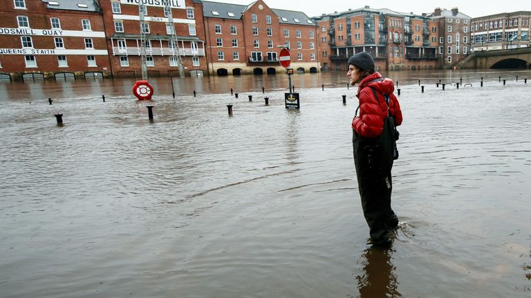 A person stands in flood water in York as Storm Christoph is set to bring widespread flooding