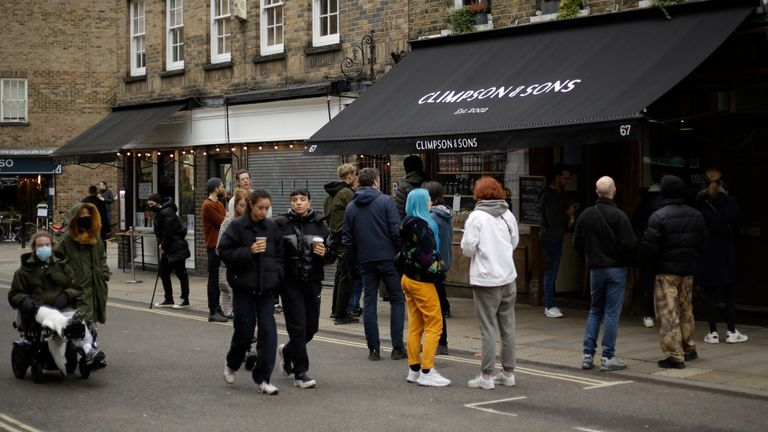 People queue up and wait for their takeaway orders outside a London cafe