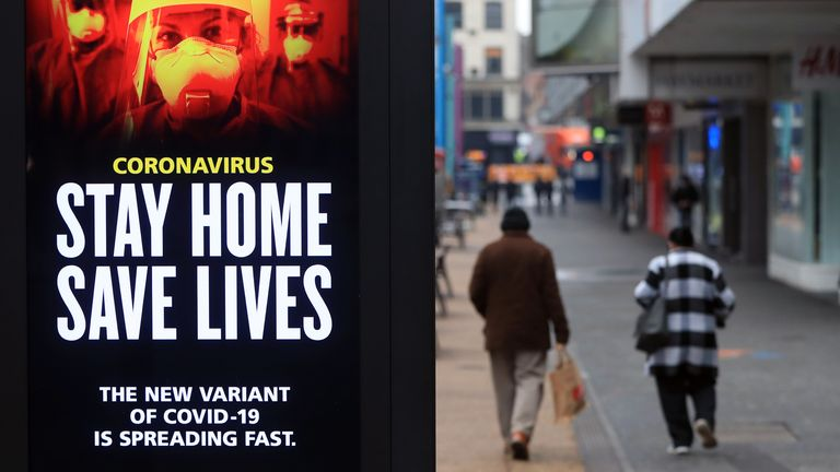 People pass a Stay Home, Save Lives electronic board in Leicester during England's third national lockdown to curb the spread of coronavirus.