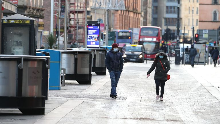 People walk along a near empty Argyle Street in Glasgow city centre the morning after stricter lockdown measures came into force for mainland Scotland.