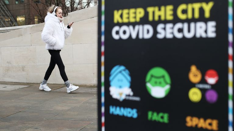 A woman walks past a coronavirus information sign outside London Bridge station, the morning after Prime Minister Boris Johnson set out further measures as part of a lockdown in England in a bid to halt the spread of coronavirus.
