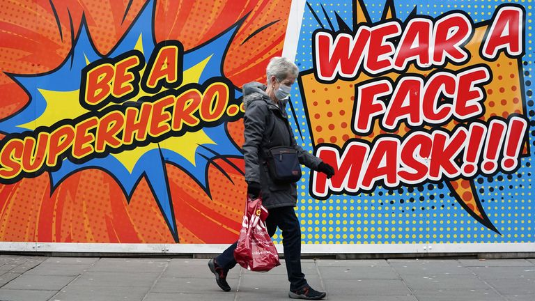 A person walks past a sign telling people to wear a face mask in Nottingham